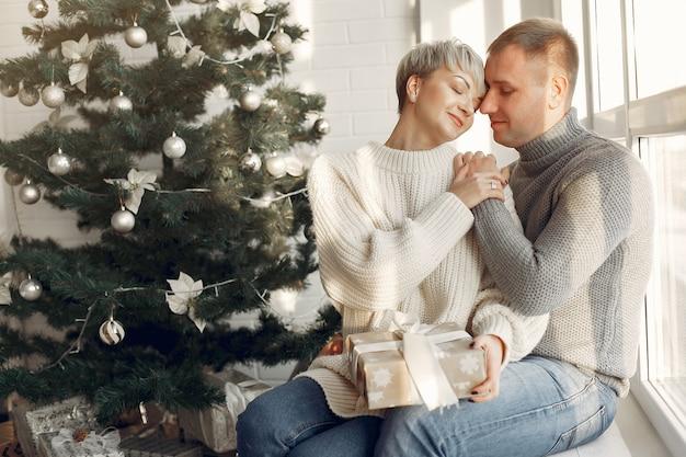 家にいる家族。クリスマスの飾りの近くのカップル。灰色のセーターを着た女性。