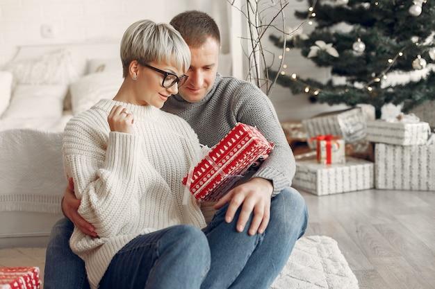 Семья дома. пара возле рождественских украшений. женщина в сером свитере.