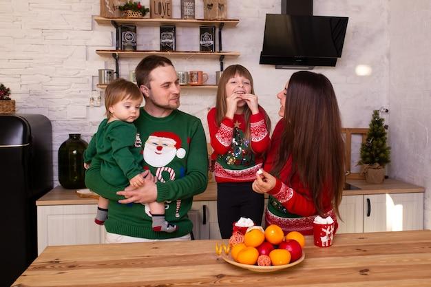 クリスマスを待っている台所で家にいる家族