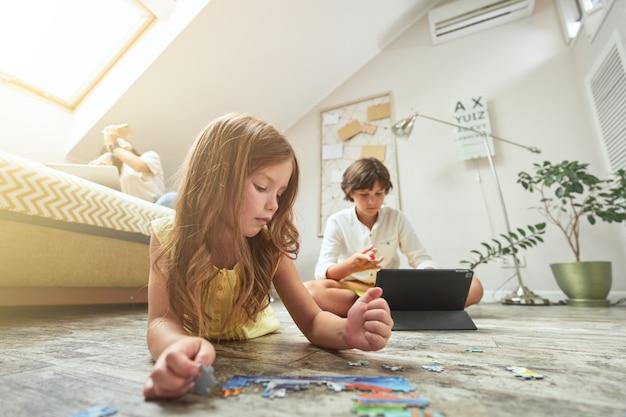 自宅の家族リビングルームの床に横になってパズルで遊んでいる少女