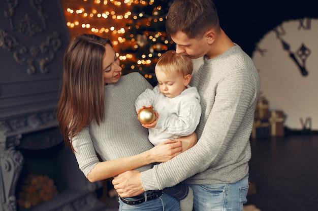 Семья дома возле елки