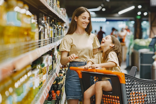 슈퍼마켓에서 가족. 갈색 t- 셔츠에있는 여자. 사람들은 제품을 선택합니다. 딸과 어머니.