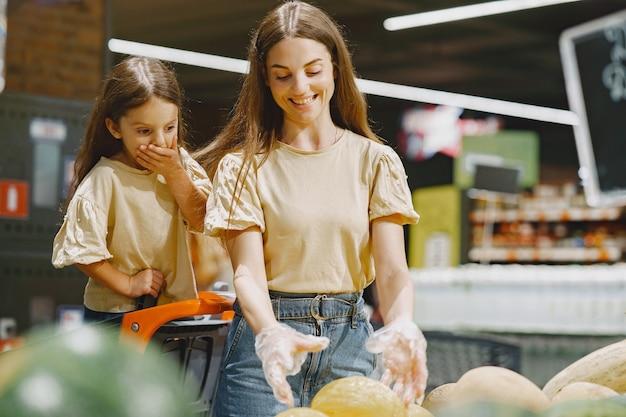 슈퍼마켓에서 가족. 갈색 t- 셔츠에있는 여자. 사람들은 야채를 선택합니다. 딸과 어머니.
