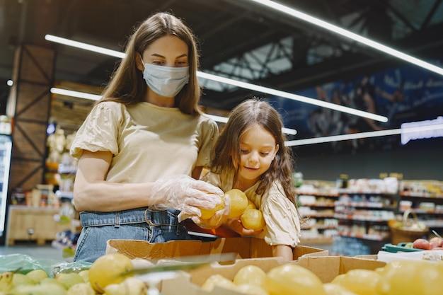 슈퍼마켓에서 가족. 보호 마스크에 여자입니다. 사람들은 야채를 선택합니다. 딸과 어머니. 코로나 바이러스.