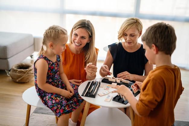 子供たちとボードゲームをしているテーブルの家族。レズビアンのカップル、保育園、子供の頃のコンセプト。