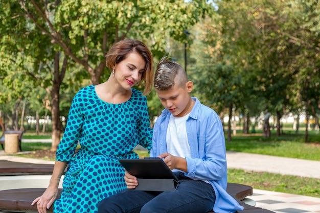 Семья, дополненная реальность, технологии и люди концепции - мать и ее сын, сидя на скамейке в парке и наслаждаться телефоном