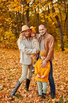 Family in autumn forest, spend free time together outdoors on fresh air