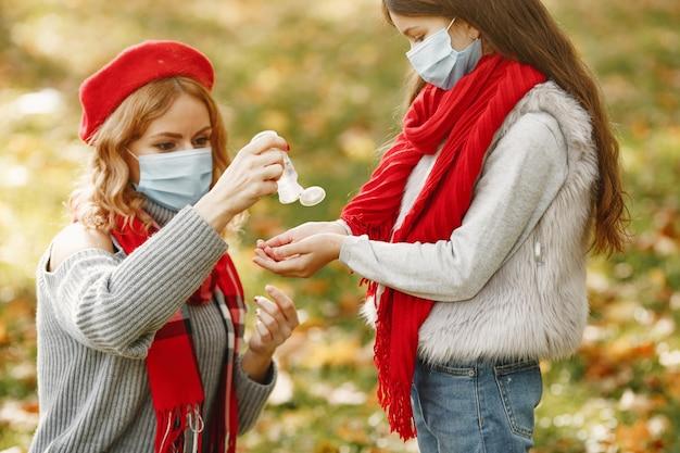 Famiglia in un parco d'autunno. tema coronavirus. madre con figlia. le persone usano l'antisettico.