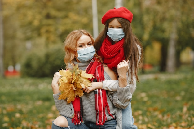 Family in a autumn park. coronavirus theme. mother with daughter.