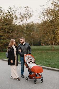 Famiglia in un parco d'autunno. uomo in giacca nera. bambina sveglia con i genitori.