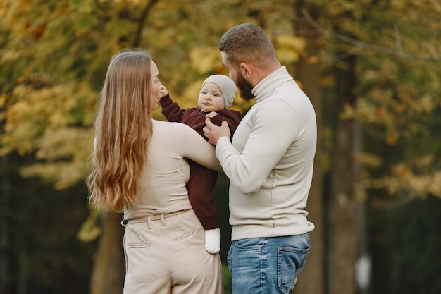 Family in a autumn park. man in a brown sweater. cute little girl with parents.