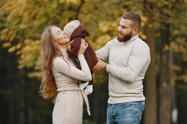 Famiglia in un parco d'autunno. uomo con un maglione marrone. bambina sveglia con i genitori.