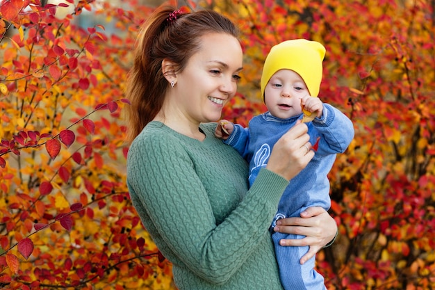 Family in a autumn park mother in a green sweater cute little girl
