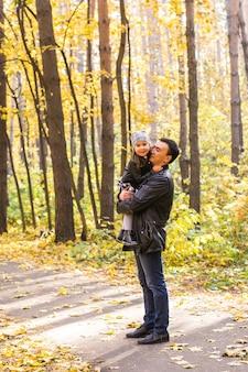 家族、秋、人々の概念-秋の公園を歩いている父と娘。お父さんの手に娘
