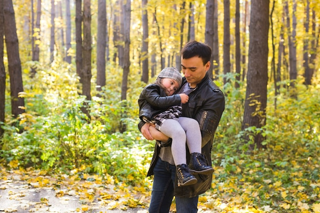 家族、秋、人々の概念-秋の公園を歩いている父と娘。