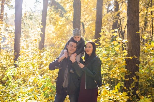 家族、秋、人々の概念-秋の公園を歩いている若い家族。お父さんの肩に座っている娘。
