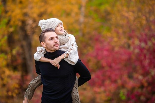 Семейные осенние выходные. молодой отец и его маленькая дочь вместе в осеннем парке