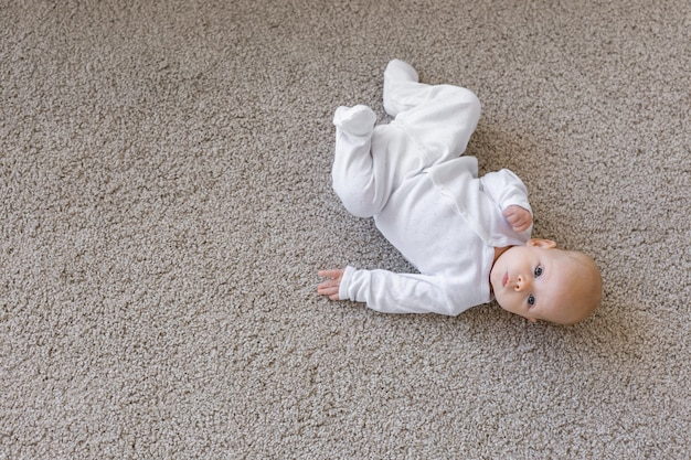 Концепция семьи, ребенка и младенца - крупным планом портрет маленького ребенка на полу