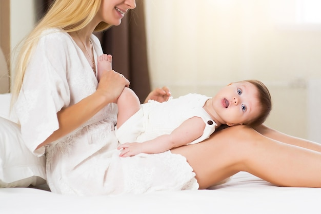 Family, baby and parenthood concept. happy smiling young mother with infant babygirl at home spend time together