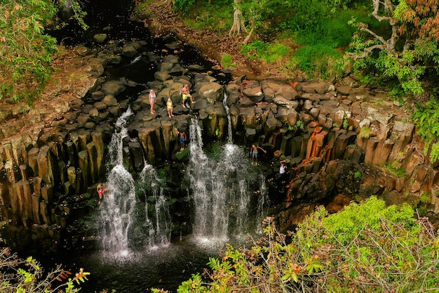 Family on the background of the rochester waterfall on the island of mauritius from a height.