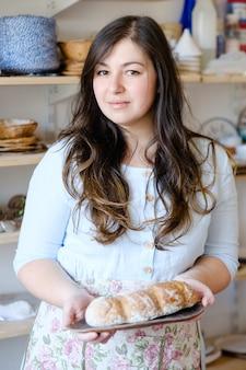 가족 빵집. 쟁반에 천연 유기농 빵 덩어리를 들고 여자. 전통 베이킹 공예 프리미엄 사진