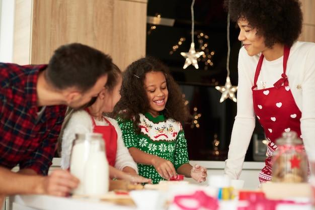 Семья печет печенье на рождество вместе