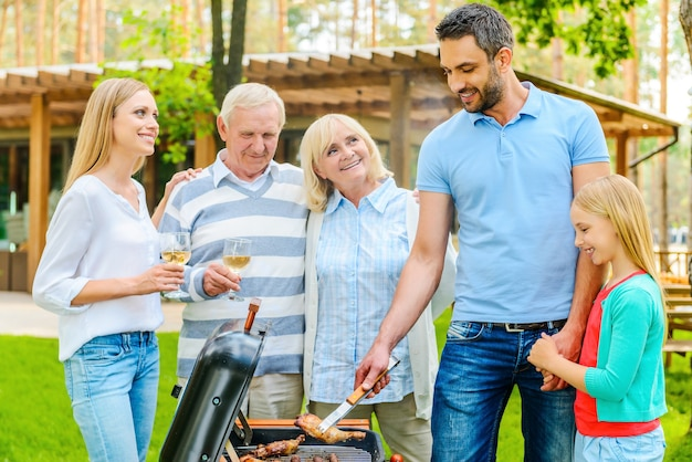 Family barbeque. happy family of five people barbecuing meat on grill on the back yard of their house