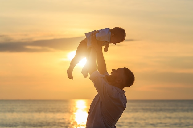 Family on the beach concept, father playing and carrying his son on the tropical beach