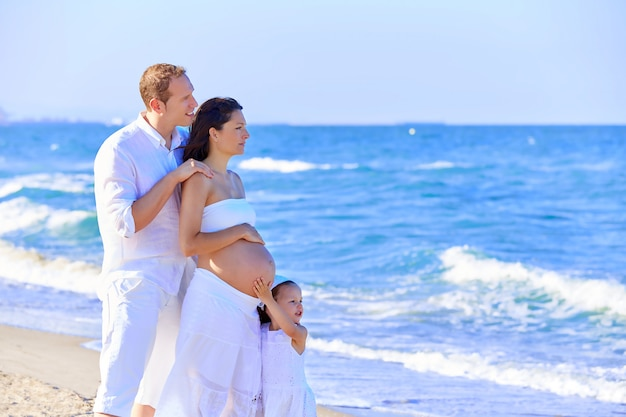 Family on the beach pregnant mother