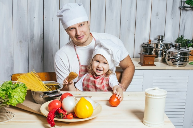 Family, beautiful daughter dad at home the kitchen laughing and preparing food together