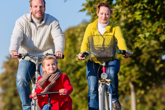 Family on bicycle tour in park