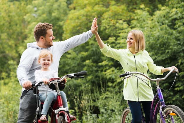 Family on bicycles giving high five