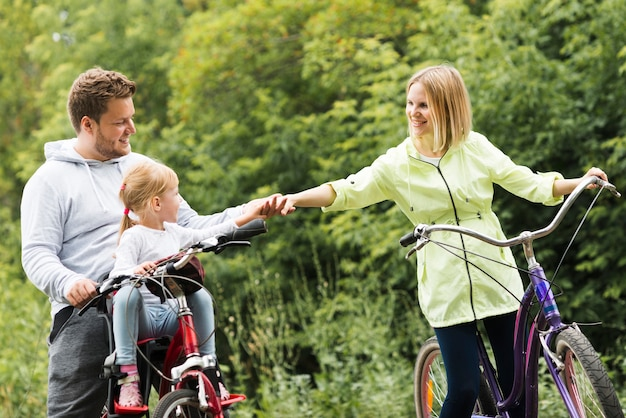 Family on bicycles holding hands