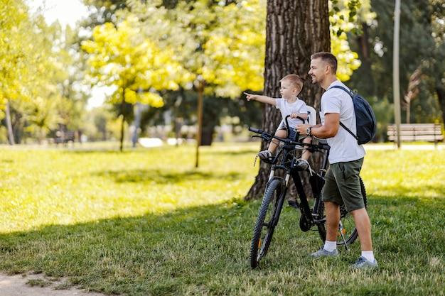 家族で自転車に乗る。父と息子は、晴れた夏の日に緑豊かな公園でサイクリングを休憩します。帽子をかぶった幼児がバスケットに座って、男が立っている間に何かを指しています