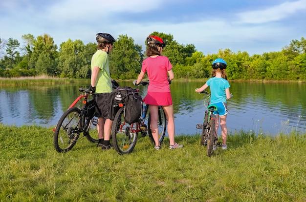 야외에서 가족 자전거 타기, 활동적인 부모와 아이 사이클링 및 아름다운 강 근처의 야외 휴식 및 가족 스포츠 및 피트니스