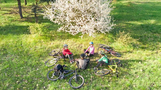 Family on bikes cycling outdoors active parents and kids on bicycles aerial view of happy family