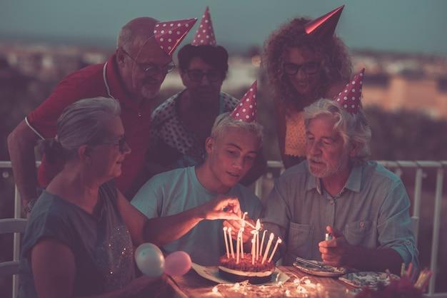 ケーキと火のキャンドルで夜の家族の誕生日のお祝い-男の子の父と祖父の家族は一緒に笑顔で楽しんで楽しんでいます