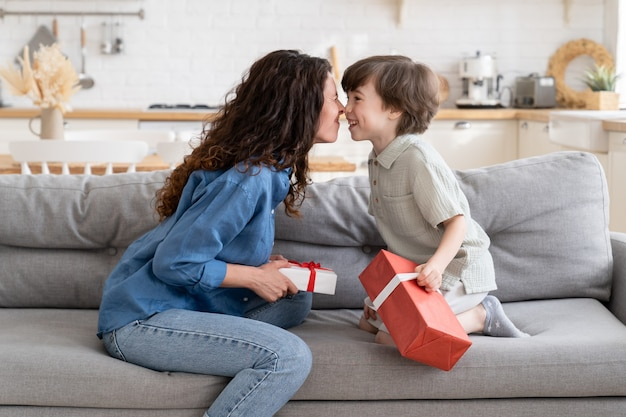Family on birthday valentines day xmas mom and son bonding sit on couch with gift boxes in hands