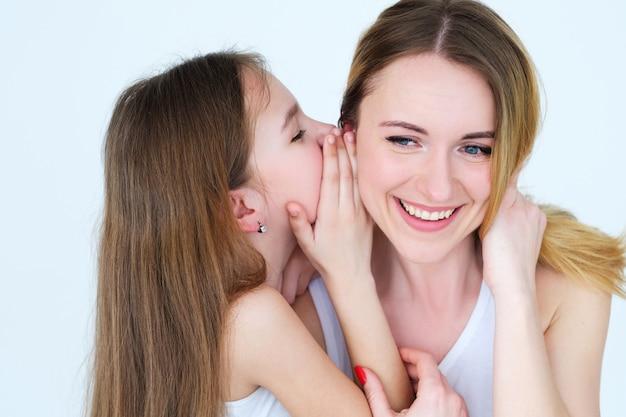 가족 유대와 비밀 공유. 어머니의 귀에 속삭이는 딸.