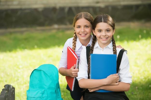 가족 결속의 시간. 함께 주제를 배우는 여학생. 즐겁게 공부하세요. 교복을 입은 행복한 소녀들. 카피북을 들고 배낭을 메고 웃고 있는 십대 학생들. 초등학교에서의 교육.
