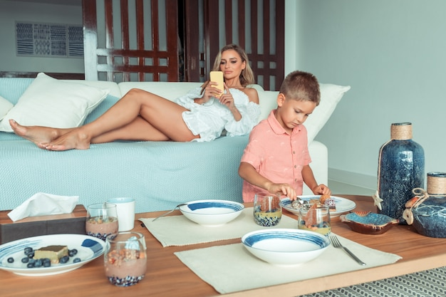 家族の朝食。若い母親が横になっていて、息子が一人で食事をしている間に電話で友達とおしゃべりしています。電話中毒。