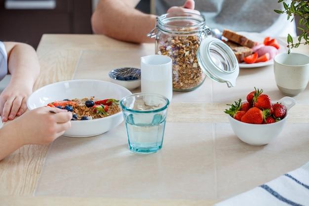 Концепция семейного завтрака. семья ест здоровую мюсли и фруктовый завтрак.