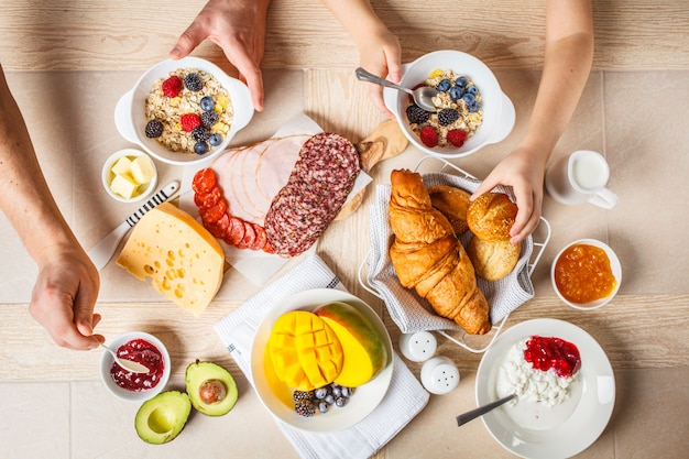 Family breakfast table with croissants, jam, ham, cheese,  butter, granola and fruit.