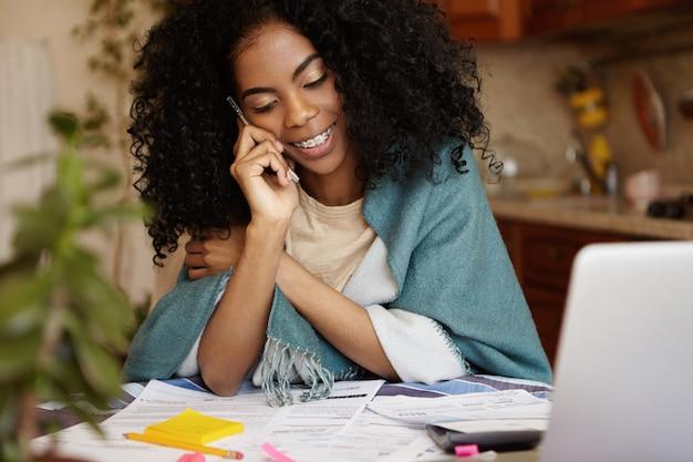 Семейный бюджет и финансы. симпатичная африканская женщина с афро-стрижкой и подтяжками разговаривает по телефону и улыбается, делая документы, подсчитывая внутренние расходы, оплачивая счета онлайн на ноутбуке