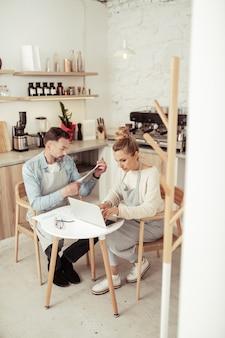 ファミリービジネス。家族の喫茶店でノートパソコンで働く集中した夫婦。