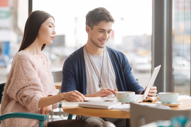 ファミリービジネス。カフェテリアに座って昼休みにラップトップで作業している素敵な若いカップル。