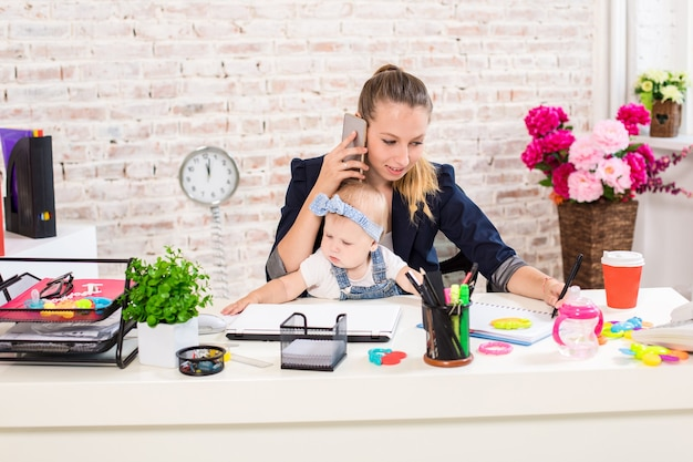 Family business  telecommute businesswoman and mother with kid is making a phone call