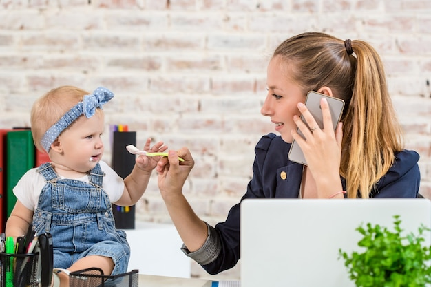 Family business - telecommute businesswoman and mother with kid is making a phone call