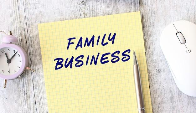 나무 작업 테이블에 누워 노트북에 작성 된 family business 텍스트.
