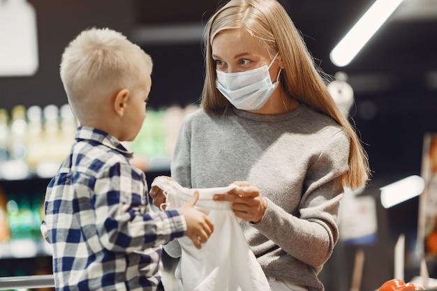 식료품을 사는 가족. 회색 스웨터에 어머니. 의료 마스크에 여자입니다. 코로나 바이러스 테마.